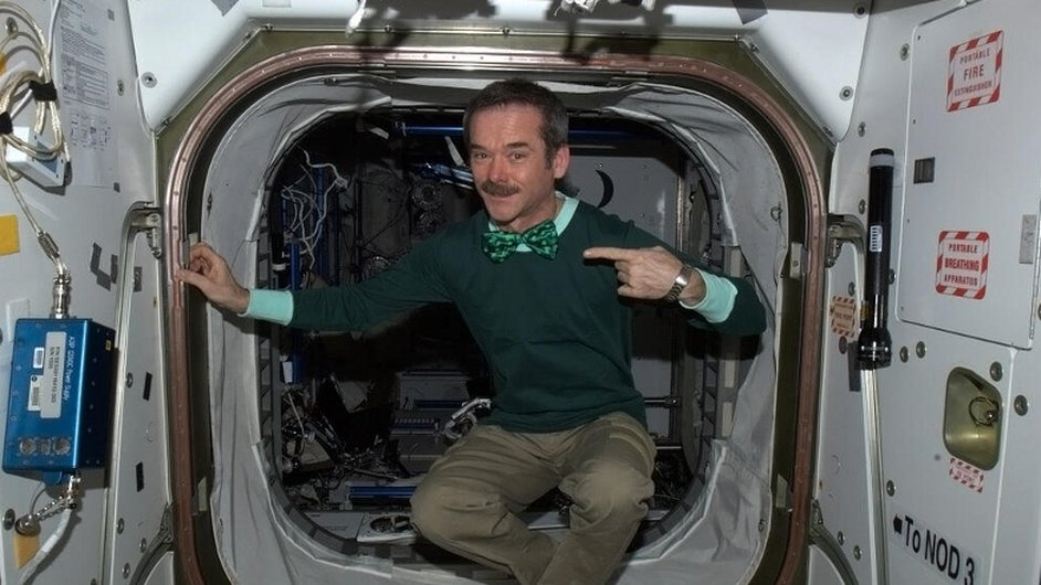 Astronaut Chris Hadfield takes off his jump suit and puts on his green bow tie to celebrate St Patrick's Day at the International Space Centre