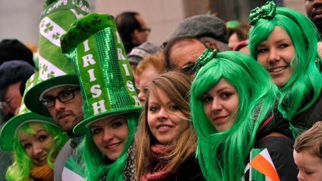 Parade-goers watch as marching bands make their way up Fifth Avenue in New York City