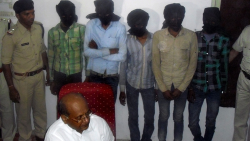 Indian Deputy Inspector General DK Arya (C) sits in front of five hooded suspects during a press meeting in Datia