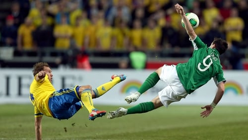 Andreas Granqvist of Sweden and Ireland's Shane Long clash in the air