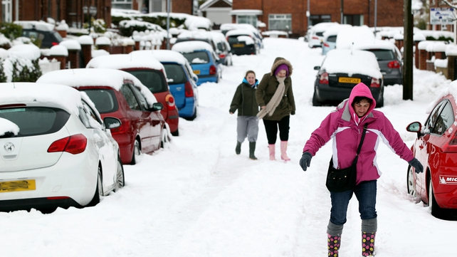 People walk through heavy snow in Glengormley in Antrim