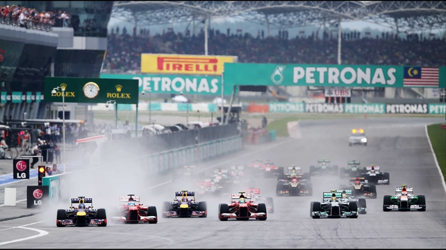 Sebastian Vettel (l) leads the field into turn one of the Malaysian Formula One Grand Prix at the Sepang Circuit