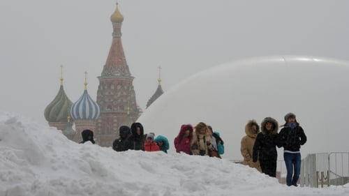 Tourists walk between snowdrifts at the Red Square in Moscow with a huge temporary dome covering the mausoleum of Soviet state founder Vladimir Lenin (R) rising in the background