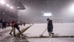 Event staff clear snow near the corner of the field even as play continues in the snow during a FIFA 2014 World Cup Qualifier match between Costa Rica and United States