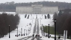 Pedestrians walk through the snow at the Stormont estate in Belfast, Northern Ireland on Saturday