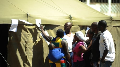 People check for results outside a polling station in Mbare township after voting for a new constitution