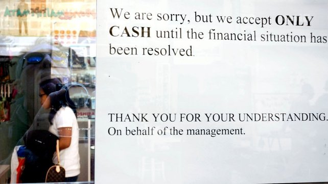A sign hangs in a window of a store in Nicosia informing shoppers that cash will only be accepted