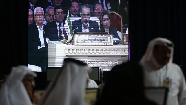 Moaz Alkhatib appears on a screen as he addresses the opening of the Arab League summit in the Qatari capital Doha