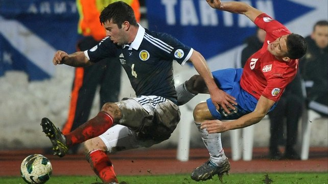Scotland's Grant Hanley gets the better Dusan Tadic