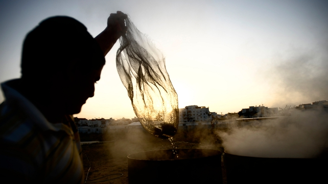 An Israeli man immerses cooking utensils into boiling water to make them kosher for the Jewish festival of Pesah (Passover)