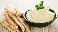 Hummus and Crispy Pitta Bread - Serve the dip with an extra drizzle of olive oil and sprinkle of coriander on top and the crispy baked pittas on the side.