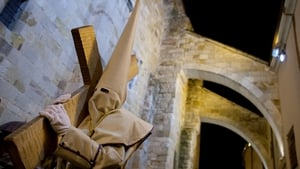 A man carries a cross during the Holy Week procession of the Cofradia Jesus Yacente in Zamora, Spain