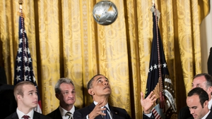 US President Barack Obama heads a football during a ceremony to honour teams from Los Angeles