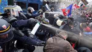 Riot police spray teargas on demonstrators during clashes on the Champs-Elysees in Paris