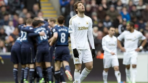 Miguel Michu reacts as Spurs players celebrate a goal