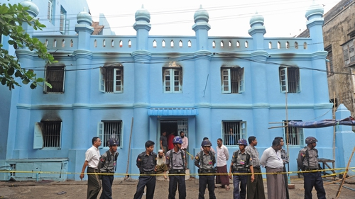 Police stand guard outside the school where at least 13 children died
