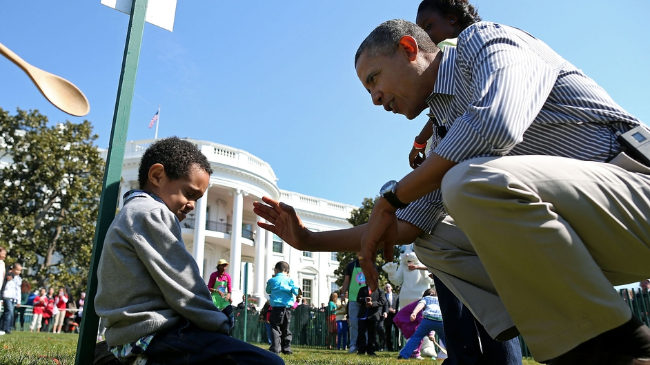 US President Barack Obama comforts crying Donaivan Frazier during the annual Easter Egg Roll on the White House tennis court