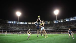 Chris Judd of the Blues contests for the ball against Luke McGuane of the Tigers during the round one AFL match between Carlton and Richmond
