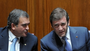 Miguel Relvas (L) chats with Portuguese Prime Minister Pedro Passos Coelho during a parliamentary session last year