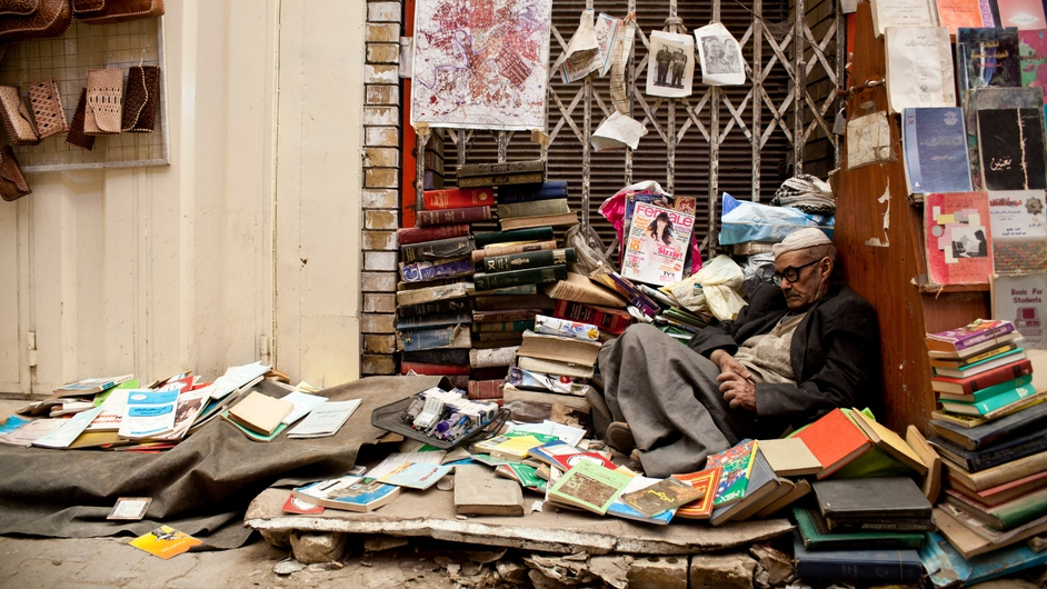 A bookseller sleeps at his stall in the Muntanabi Street area in Baghdad
