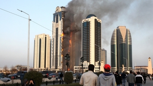 Chechen people look at a burning skyscraper in central Grozny