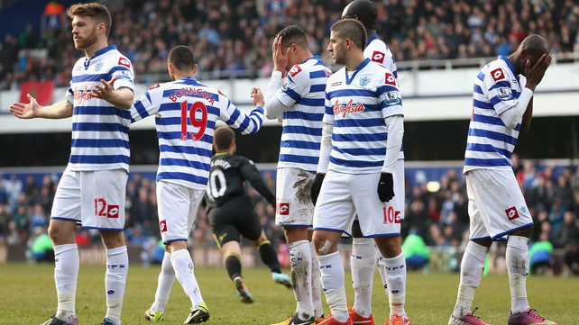 Shaun Maloney runs away in celebration as the QPR players take in Wigan's last-minute equaliser