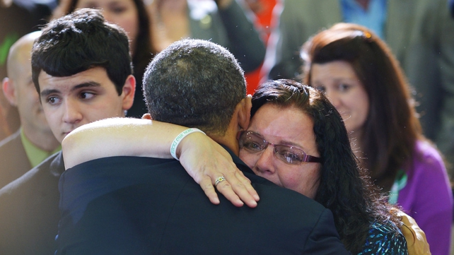 Mr Obama hugs an audience member after speaking at the University of Hartford
