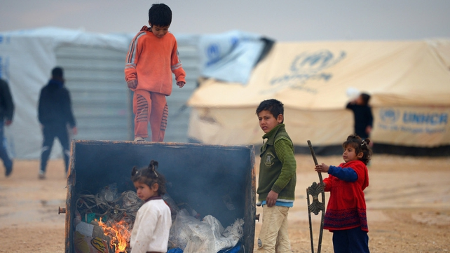 Syrian children get a heat from a burning rubbish bin in the Za'atari refugee camp in Jordan