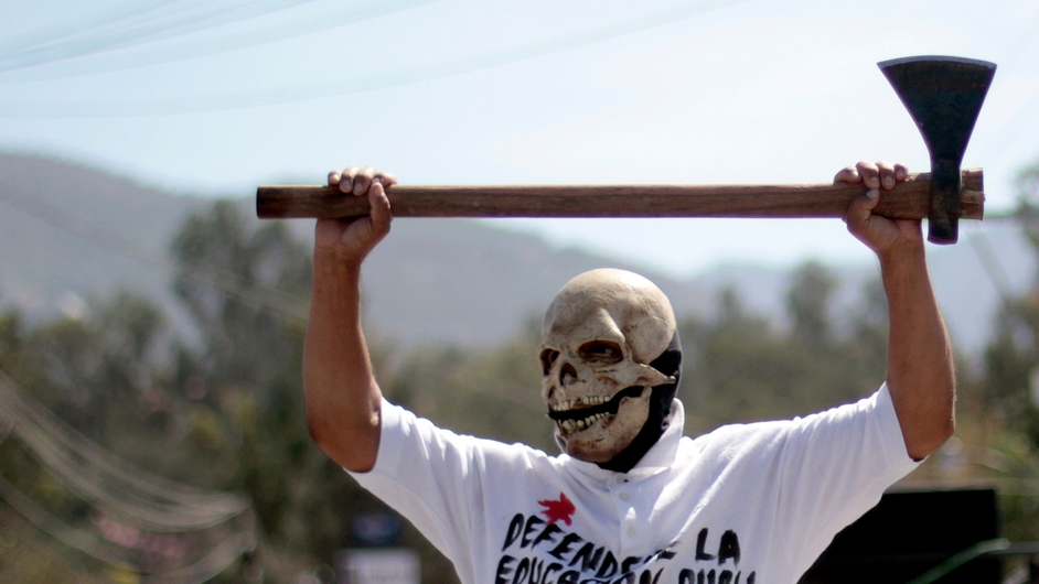 A masked teacher member of the National Coordinating Committee of Education Workers (CNTE) marches along the highway between Mexico City and Acapulco in Chilpancingo, Guerrero state, Mexico