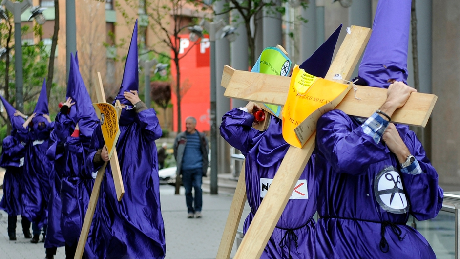 Justice civil servants of Baracaldo's court, wearing penitents costumes and carrying wooden crosses, take part in a protest against the government's spending cuts in justice services outside the court in the Northern Spanish Basque city of Baracaldo