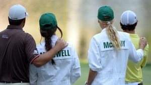 Rory McIlroy of Northern Ireland hugs his caddie Caroline Wozniacki as Graeme McDowell of Northern Ireland hugs his caddie and fiance Kristin Stape