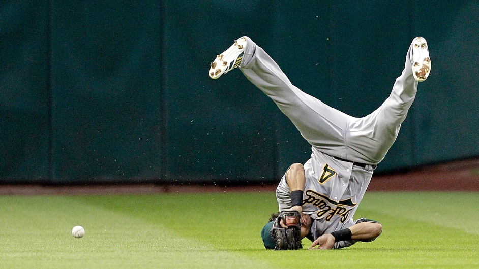Coco Crisp of the Oakland Athletics dives but comes up short on a sinking line drive hit by Chris Carter of the Houston Astros in the first inning at Minute Maid Park in Houston, Texas