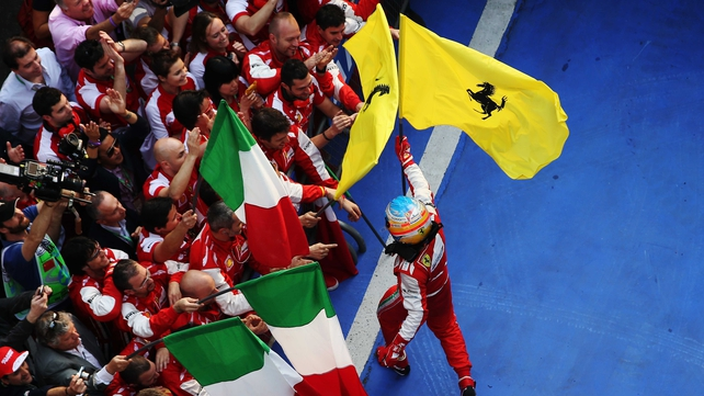 Fernando Alonso of Spain and Ferrari celebrates in parc ferme with teammates after winning the Chinese Grand Prix at the Shanghai International Circuit