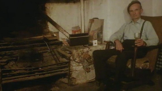 An old man sits in an armchair by a large hearth.