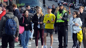 Competitors and spectators are led away from the Boston marathon course