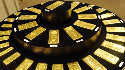 Gold rises on weakening dollar; heading for best year since 2010