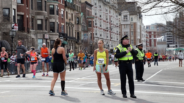 Police and runners stand in shock near Kenmore Square in Boston shortly after yesterday's attacks