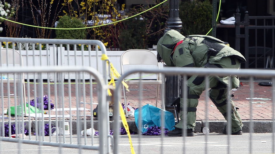 A member of the bomb squad investigates a suspicious item on the road near Kenmore Square in Boston