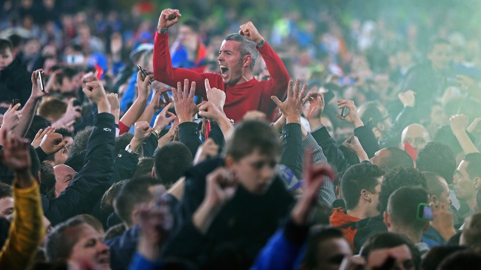 Kevin McNaughton is hoisted above the celebrating Cardiff City supporters after gaining promotion to the English Premier League