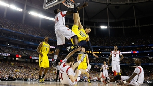 Jordan Morgan of the Michigan Wolverines gets upended against the Louisville Cardinals during the 2013 NCAA Men's Final Four Championship at the Georgia Dome