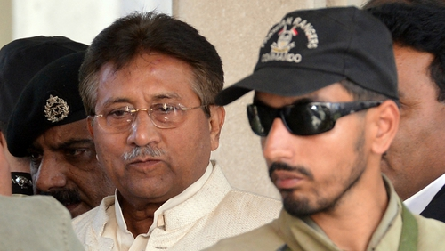 Former Pakistani president Pervez Musharraf is escorted by paramilitary soldiers as he leaves the Pindi High Court
