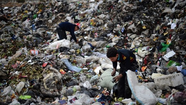 Young Syrian boys collect plastic and metal items in a garbage dump in the northern Syrian city of Aleppo