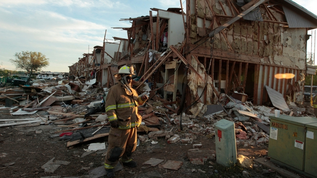 Fire Department personnel walk among the remains of an apartment complex next to fertilizer plant
