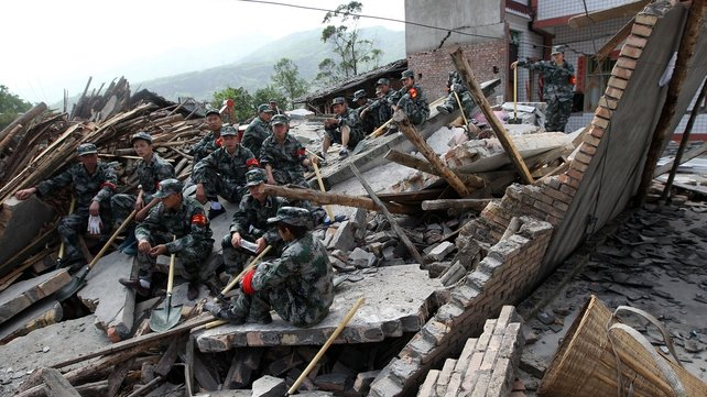 Rescuers sit on ruins of a house in the Longmen area of Sichuan