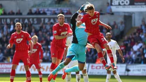 Swansea 'keeper Michel Vorm collects despite the efforts of Adam Lallana