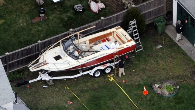 FBI agents examine the boat the day after the suspect was captured