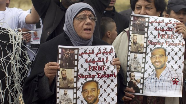 Layla Essawi, the mother of Samer Essawi, holds up his poster as she and others take part in a solidarity sit-in