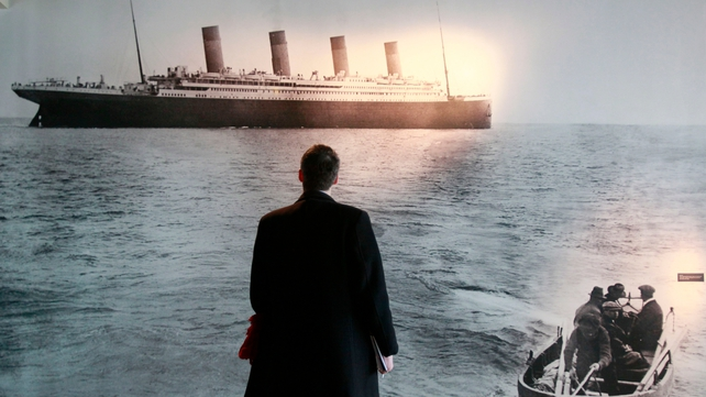 A man stands in front of a photograph taken by Frank Browne of the Titanic departing Queentown on 11 April, 1912