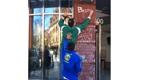 Charles Doherty writes 'Boston you're my home' at a pop up memorial in the city