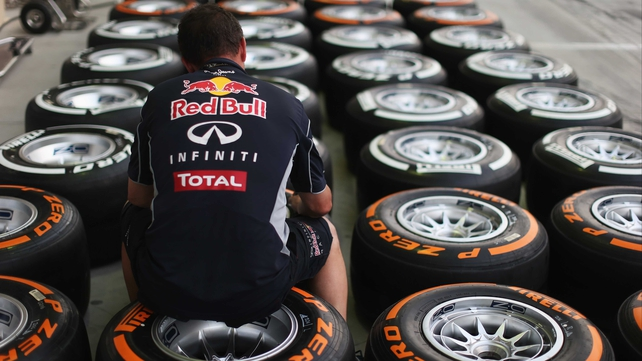 A Red Bull Racing mechanic works on wheels and Pirelli tyres in the paddock ahead of the Bahrain GP